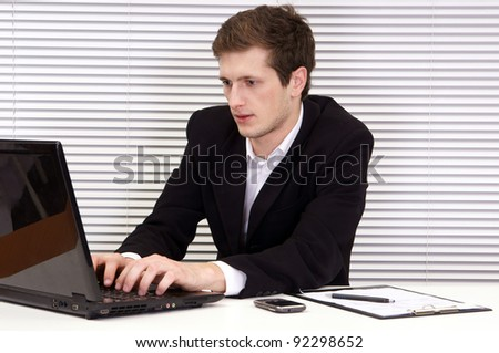 cute young businessman sitting at table in office - stock photo