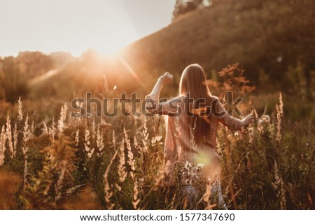 Cute young caucasian girl with long fluffy hair in a field at sunset. Beautiful young woman with brown hair dancing in a field at sunset. Freedom and nature concept.Soft focus
