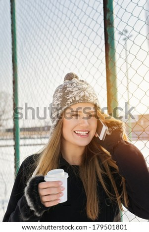 Cute young Caucasian teenage woman talking on the phone laughing holding a takeaway coffee cup smiling. Outdoors winter portrait of beautiful teenage girl speaking on the phone.