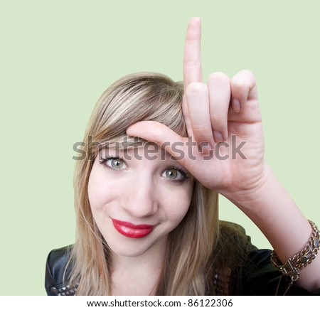 Cute young Caucasian woman makes loser sign on her forehead over green background