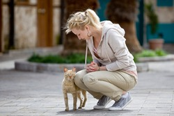 Cute young caucasian woman stroking a cat on the street and smiling, cat looking at camera. Portrait of pretty young blonde female playing with a cat on city street