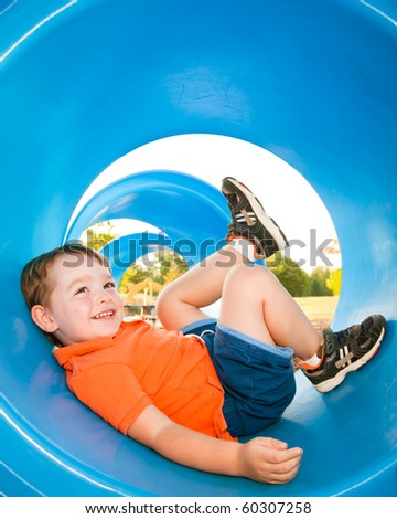 Cute young child boy or kid playing in tunnel on playground.