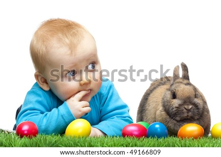 Cute young child is lying in meadow together with Easter bunny and colorful Easter eggs in meadow. Isolated on white Background.