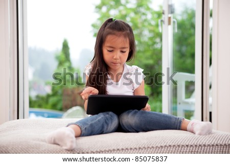 Cute young child using a digital tablet in a home interior with large window