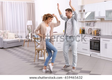 Cute young couple dancing at home #659465632