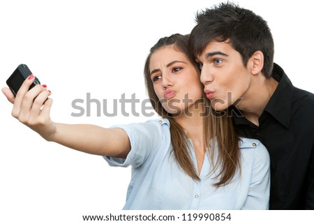 Cute young couple having fun taking self portrait.Isolated on white.
