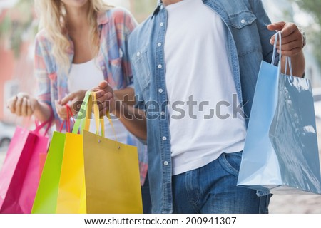 Cute young couple holding shopping bags on a sunny day in the city