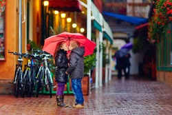 cute young couple kissing under the rain