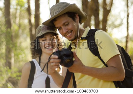 Cute young couple looking at pictures of their hiking trip