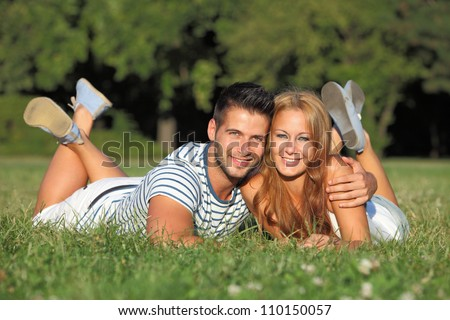 Cute young couple lying in a park