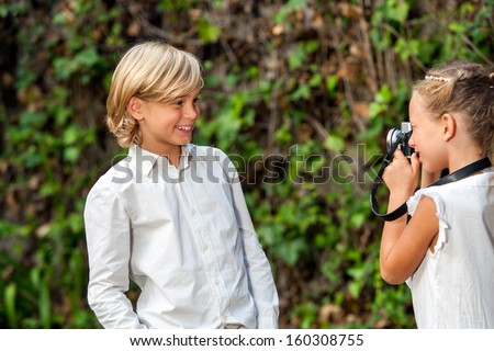 Cute young couple playing around with camera at photo shoot outdoors.