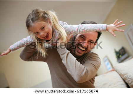 Cute young daughter on a piggy back ride with her dad. Looking at camera. ストックフォト ©
