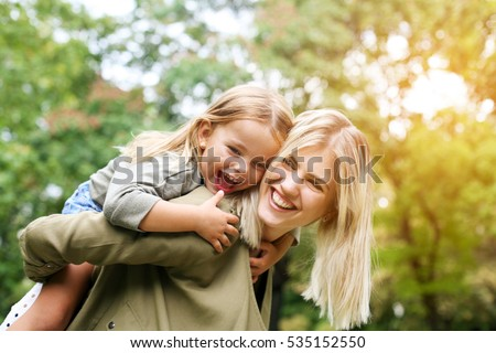 Cute young daughter on a piggy back ride with her mother. ストックフォト ©