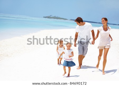 Cute young family running on the beach together