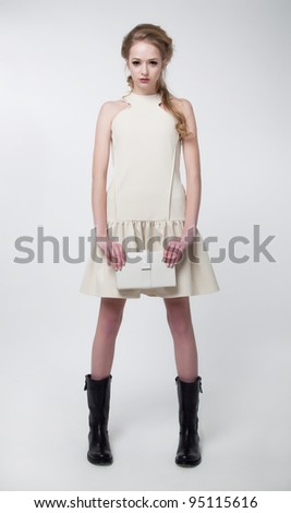 Cute young fashion model woman in modern dress on white background posing