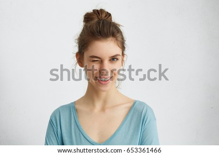 Cute young female with delicate features having hair tied in knot wearing blue sweater blinking her eyes with pleasure having happy expression. Facial expressions and people emotions concept