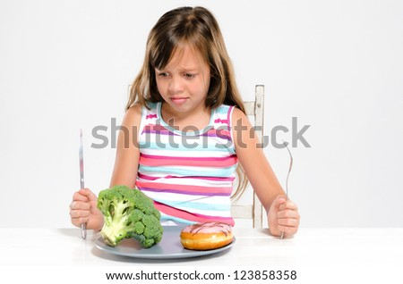 Cute young girl child making a choice between healthy broccoli vegetable and unhealthy sugary donut