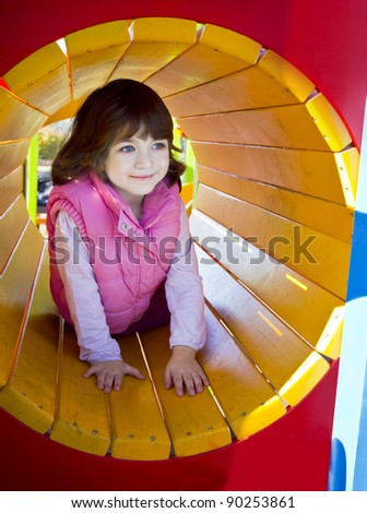 Cute young girl enjoys playing in tunnel in a children's playground