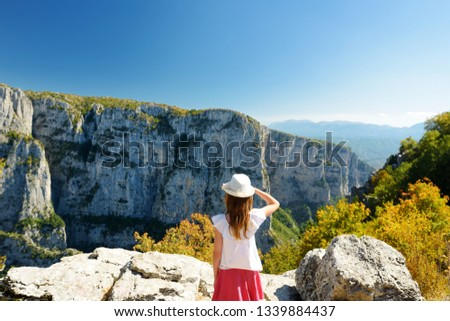 Cute young girl exploring Vikos Gorge, a gorge in the Pindus Mountains of northern Greece, lying on the southern slopes of Mount Tymfi, one of the deepest gorges in the world. Zagori region, Greece. #1339884437