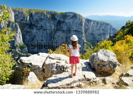 Cute young girl exploring Vikos Gorge, a gorge in the Pindus Mountains of northern Greece, lying on the southern slopes of Mount Tymfi, one of the deepest gorges in the world. Zagori region, Greece. #1339888982