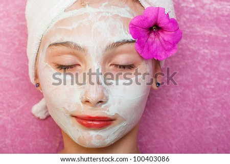 Cute young girl getting pampered with a deluxe spa treatment including facial mask.