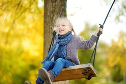Cute young girl having fun on a swing in sunny autumn park. Family weekend in a city. Fall outdoor activities for children.