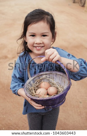 Cute young girl holding basket of fresh organic chicken eggs, Easter activity for kids, homeschooling montessori education