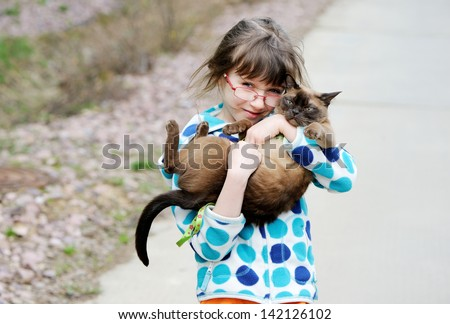 Cute young girl holding her kitty during a walk outside