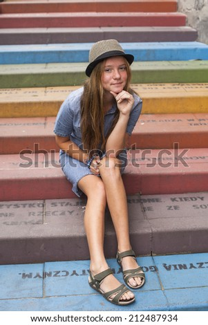 Cute young girl in a hat sitting on the stairs outdoors.