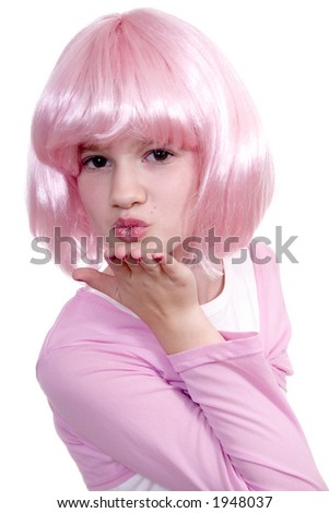 Cute young girl in pink wig blowing a kiss isolated against a white backdrop.