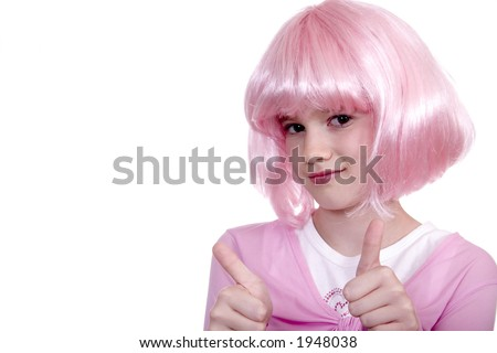 Cute young girl in pink wig giving thumbs up signal isolated against a white backdrop.
