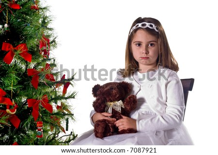 Cute young girl in white dress poses on chair with teddy bear next to a Christmas tree