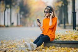 cute young girl listening music in headphones, urban style, stylish hipster teen sitting on a sidewalk on city street and choosing track on mobilephone infront of oidsity buildings, orange street