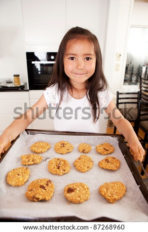 Cute young girl looking at camera with baking sheet full of raw cookies