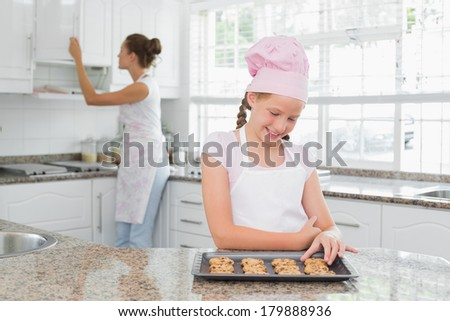Cute young girl looking at freshly prepared cookies with mother in the background at kitchen