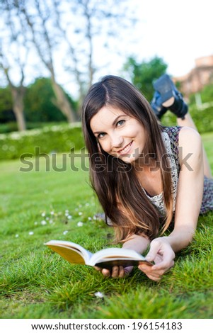 cute young girl lying on the grass, reading a book/ Girl reading book