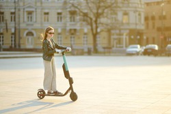 Cute young girl riding an electric scooter on sunny spring day. Electric urban transportation in Vilnius, Lithuania. Scooters for rent. Family leisure with kids.