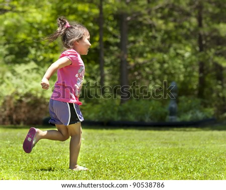Cute young girl running in the yard