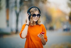cute young girl walking down old city street and listening music in headphones, urban style, stylish hipster teen hold mobile phone and and smile, orange crazy style