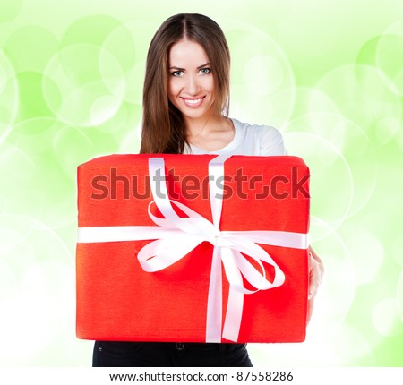 cute young girl with a gift on a green blur background