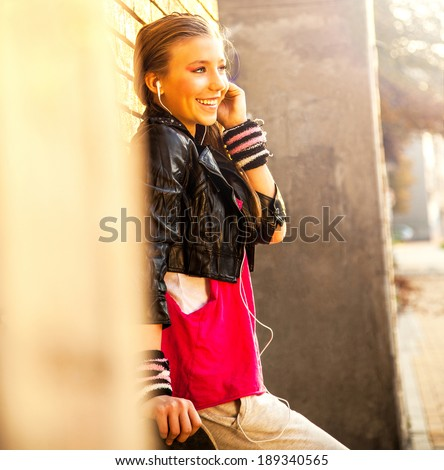 Cute young girl with earphones and skateboard, on the street