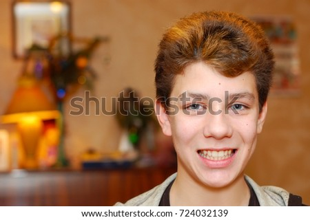 Cute young guy with healthy teeth and dyed hair smiles