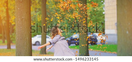 Cute young hipster millennial girl in purple blue autumn dress throwing dry fall leaves up in air with hands. Happy woman atmospheric autumn relax Freedom mind peace wind fresh breath concept banner.