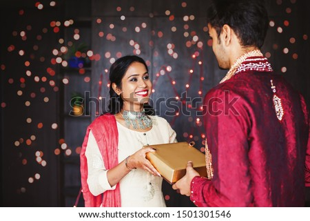 Cute young Indian woman wearing traditional ethnic clothes giving gift to a man, over festive bokeh background