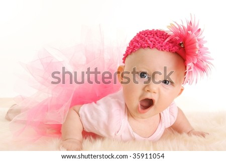 Cute young infant girl in a pink tutu and head band with an angry game face