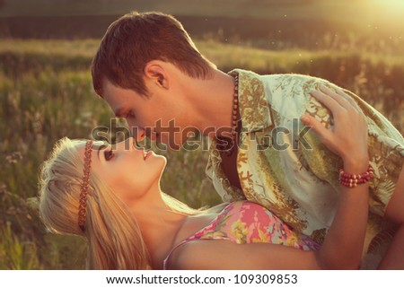 cute young man kisses beautiful woman against sunset. style of hippie