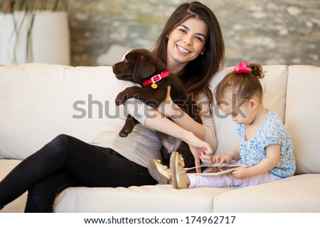 Cute young mom spending time with her daughter and a puppy