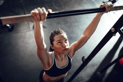 Cute young muscular girl doing pull-ups exercise at the gym.