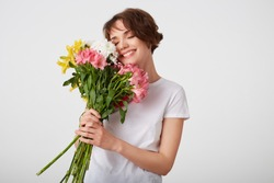 Cute young short haired girl in white blank t-shirt, holding a bouquet of colorful flowers, enjoying the smell, broadly smiling with closed eyes, standing over white background.