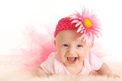 Cute young smiling infant girl in a pink tutu and flower head band